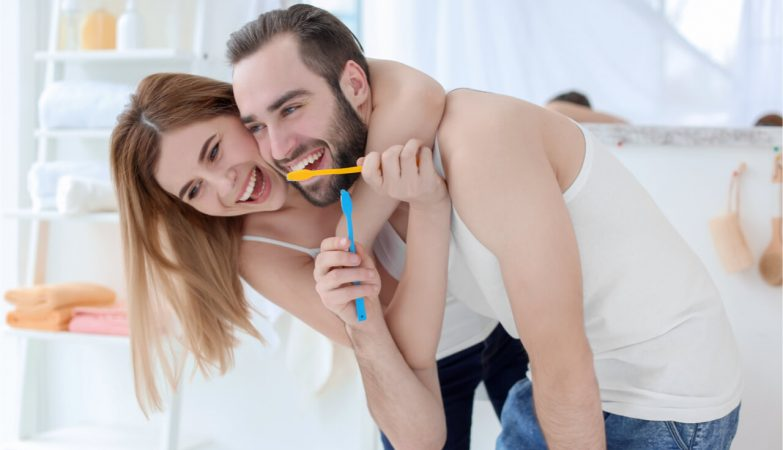 The happy couple is brushing their teeth.