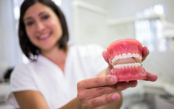 The dentist holds the denture for a photograph.